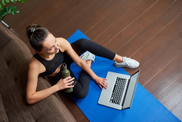 Una chica deportiva con pantalones ajustados negros y top está haciendo un entrenamiento en línea