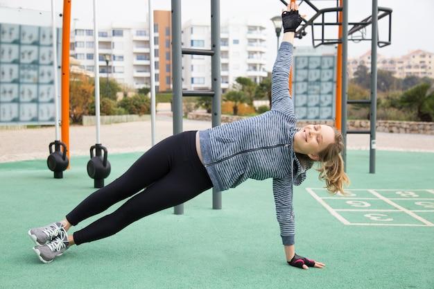 Chica deportiva positiva emocionada con entrenamiento al aire libre