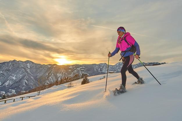 Chica deportiva con raquetas de nieve en el paisaje al atardecer