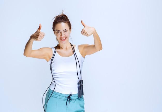 Chica deportiva sosteniendo una cuerda de saltar azul y mostrando el pulgar hacia arriba.