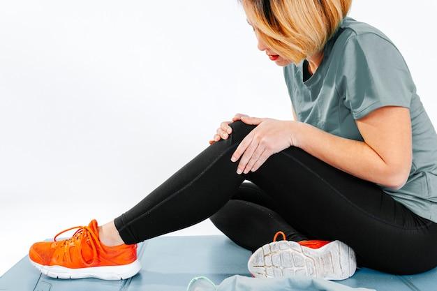 Chica deportiva teniendo problemas con el tobillo