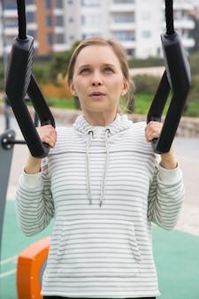 Chica deportiva tensada entrenando con correas de suspensión.