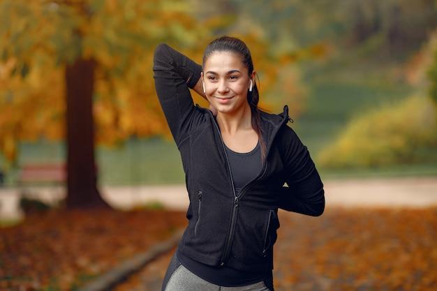 Chica deportiva en un top negro entrenamiento en un parque de otoño