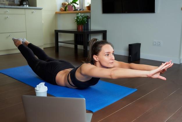 Una chica deportiva con un traje ajustado negro está haciendo el clásico ejercicio de bote para la espalda. una entrenadora en una pose de superman dirigiendo una clase de fitness en línea remota en la estera de yoga azul en casa.