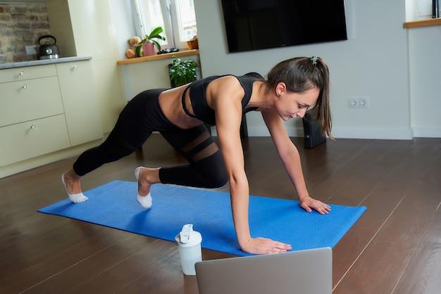 Una chica deportiva con un traje de entrenamiento negro ajustado está haciendo ejercicio para los abdominales y viendo un video de entrenamiento en línea en una computadora portátil. un entrenador que dirige una clase de fitness a distancia sobre la estera de yoga azul en casa.