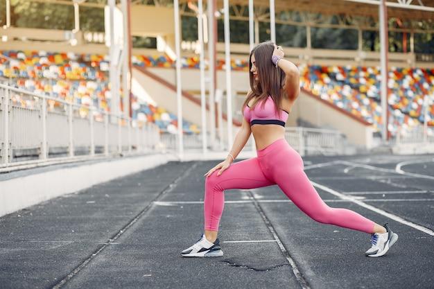 Chica deportiva en un uniforme rosa entrenamiento en el estadio