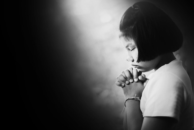 Chica deprimida y desesperada rezando en la oscuridad en tono blanco