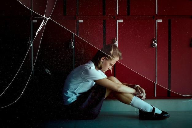 Chica deprimida de la escuela secundaria sentada junto a los casilleros en el pasillo con efecto de cristal agrietado