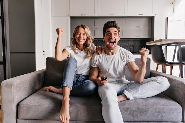 Chica descalza sentada en el sofá con novio. riendo pareja viendo la televisión.