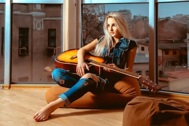 Chica descansando con una guitarra en sus manos cerca de los grandes ventanales con vistas a la ciudad. chica con guitarra. mujer tocando la guitarra. ocio con guitarra.
