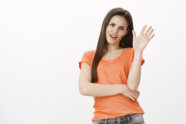Una chica descarada molesta y sin gracia rechaza la oferta, estrecha la mano en señal de rechazo, no le gusta la oferta, niega algo