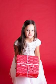 Chica descontenta en vestido blanco sosteniendo un regalo