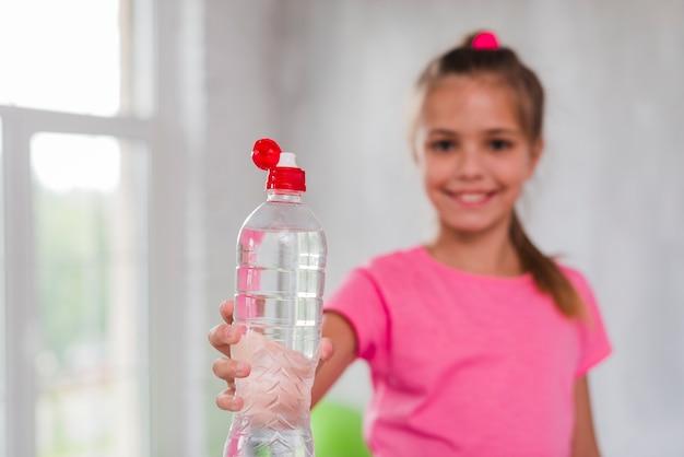 Chica desenfocada dando plástico botella de agua hacia la cámara