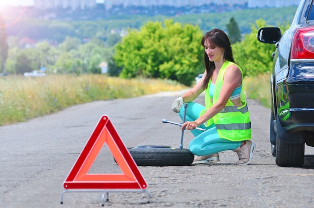 Chica desesperada con reemplazo de rueda de repuesto.