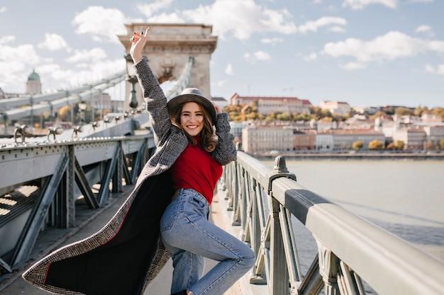 Chica despreocupada en blue jeans feliz bailando sobre fondo de arquitectura
