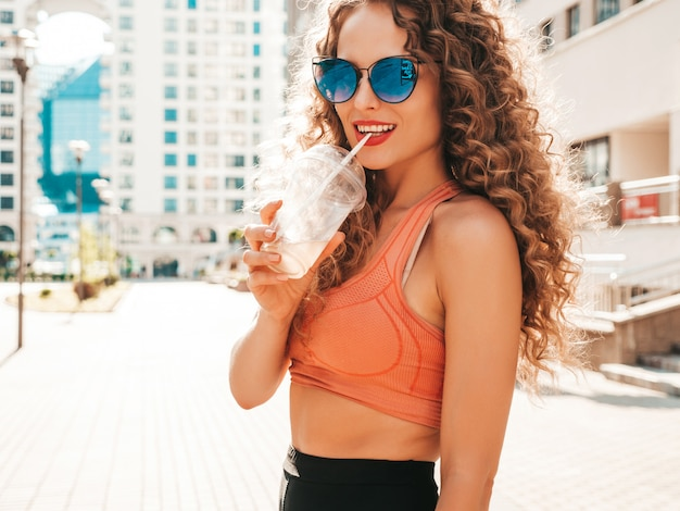 Chica despreocupada posando en la calle con una bebida