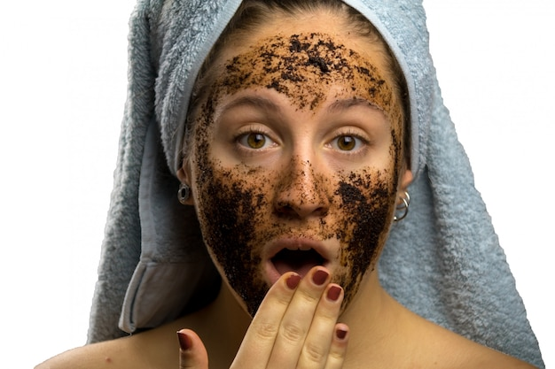Chica después de la ducha con una toalla y diferentes expresiones faciales, cara con crema de café casero