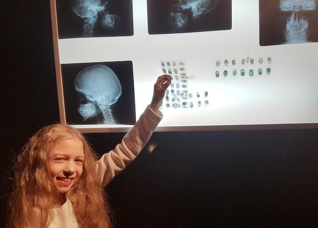 Chica detective estudiando huellas dactilares en el laboratorio