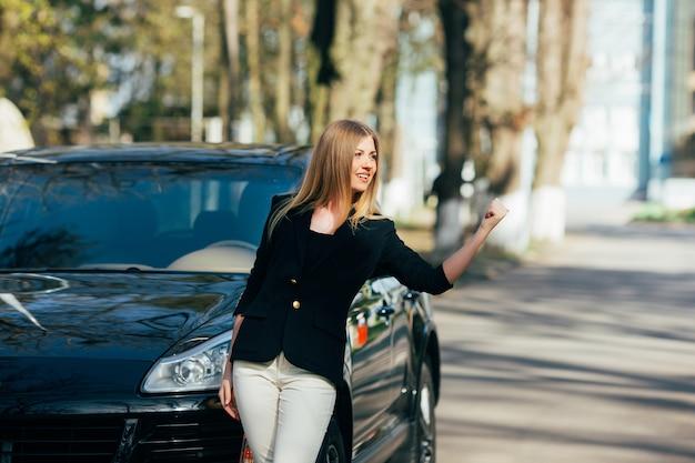 Chica detiene coches cerca de su coche destrozado