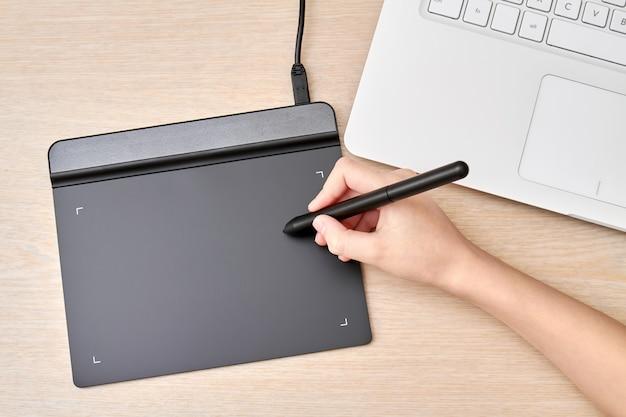 Chica dibuja en una tableta gráfica con lápiz
