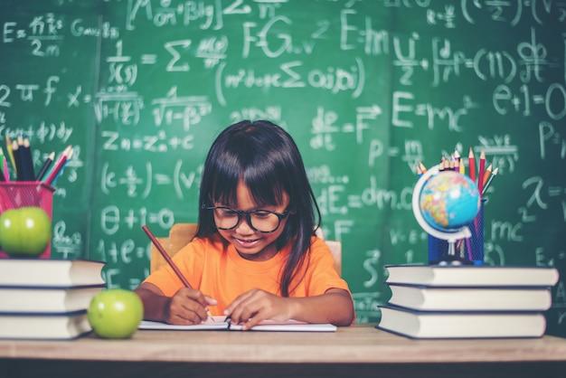 Chica con dibujo de lápices de colores en la lección en el aula
