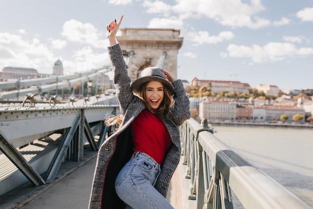 Chica dichosa bien formada en suéter rojo bailando en el puente sobre fondo borroso de la ciudad en la mañana de otoño