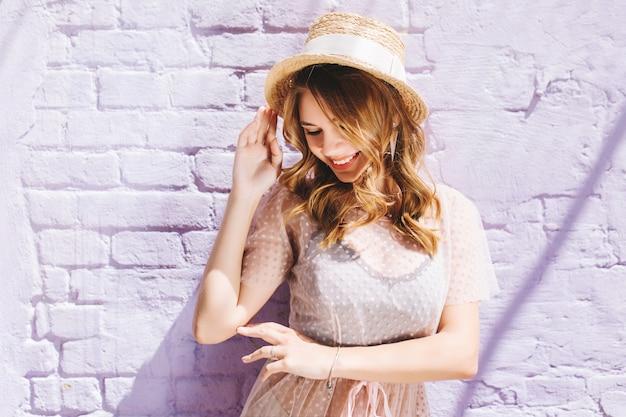 Chica dichosa en sombrero de paja vintage con cinta blanca posando con sonrisa feliz y ojos cerrados