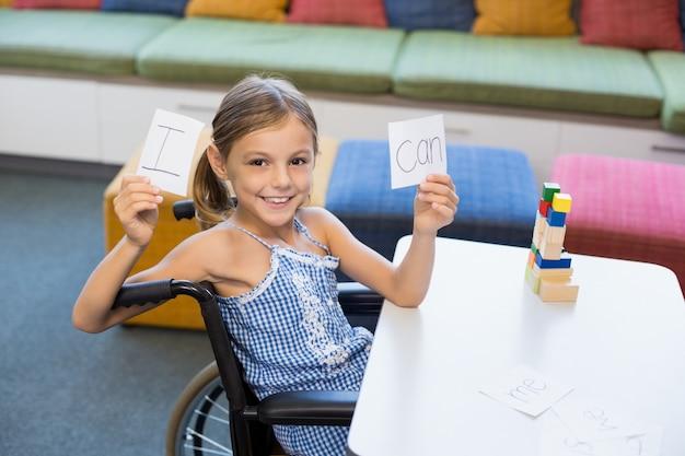 Chica discapacitada sosteniendo un cartel que dice i can en la biblioteca