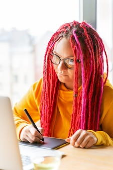Chica diseñadora, ilustradora dibuja en tableta, mira en la computadora portátil. el concepto de trabajo remoto.