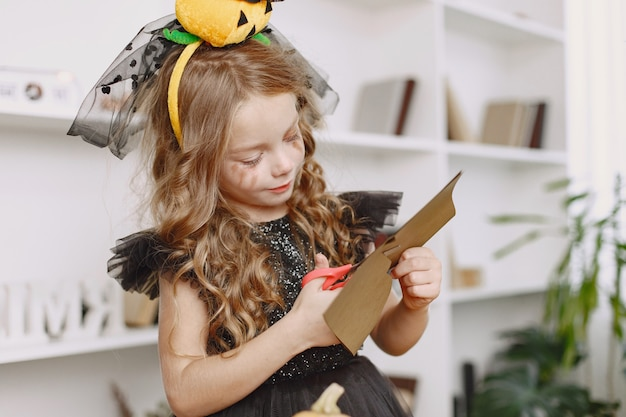 Chica en disfraces de fiesta haciendo manualidades en casa