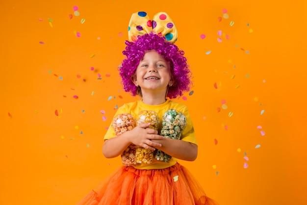 Chica con disfraz de payaso y caramelos