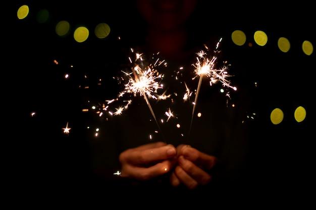 Chica disfruta jugando con una pequeña bengala de fuegos artificiales de mano, celebrando en el festival de navidad y año nuevo.