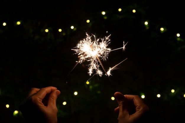 Chica disfruta jugando con una pequeña bengala de fuegos artificiales