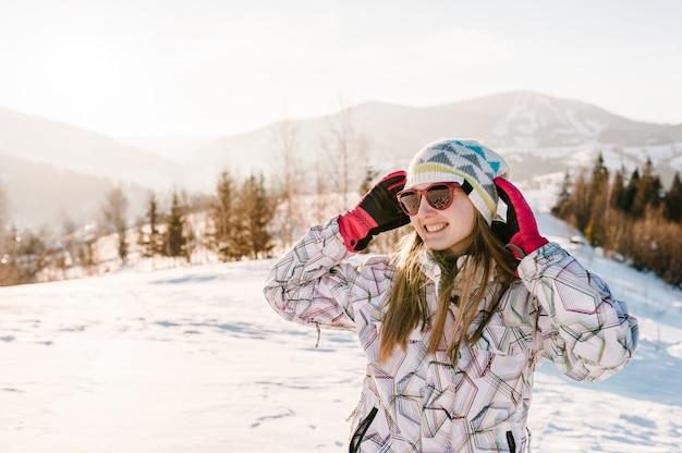 Chica disfruta de las montañas nevadas de invierno. camina en la naturaleza. temporada de heladas. concepto de vacaciones. trekking en montaña. clima frío, nieve en las colinas. excursionismo. montañero en la cima en un soleado día de invierno.