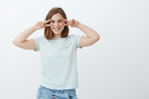 Chica disfrutando de la juventud. encantadora mujer europea joven de aspecto amistoso en camiseta casual que muestra paz o gestos disco sobre los ojos que se sienten juguetones y entretenidos colgando contra la pared gris
