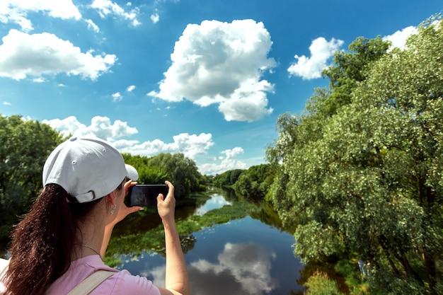 Chica dispara un hermoso paisaje en un teléfono inteligente