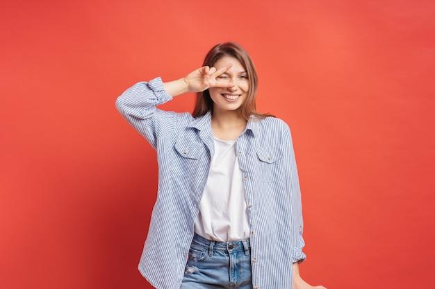 Chica divertida y despreocupada divirtiéndose aislado en una pared roja