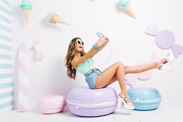 Chica divertida inspirada con camiseta sin mangas y pantalones cortos de mezclilla sentada en macarrones de juguete y haciendo selfie. riendo a señorita con gafas de sol y auriculares tomando una foto de sí misma en una habitación con un interior dulce.