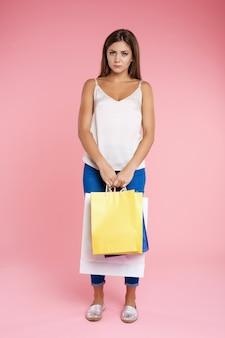 Chica divertida parece triste sosteniendo un montón de bolsas después de ir de compras