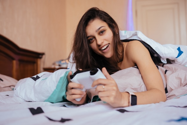 Chica divertida en ropa casual acostada en la cama y jugando videojuegos, sosteniendo el controlador en las manos