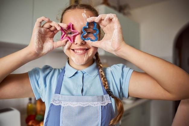 Chica divertida sonriendo y jugando con cookieshapers