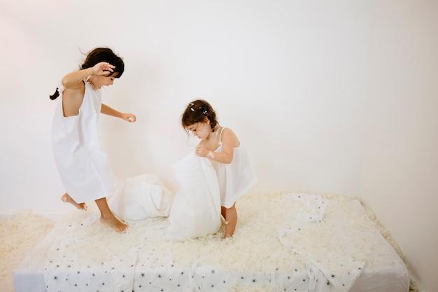 Chica divirtiéndose en el colchón con la hermana