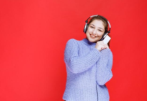 Chica dj con auriculares presentando su tarjeta de visita.