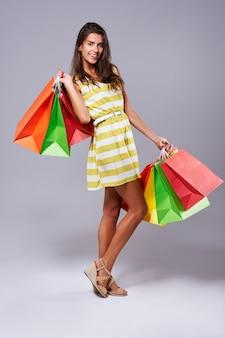 Chica doblando con bolsas después de ir de compras