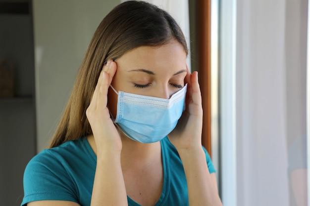Chica con dolor de cabeza aislar en casa con máscara contra la enfermedad del coronavirus 2019.