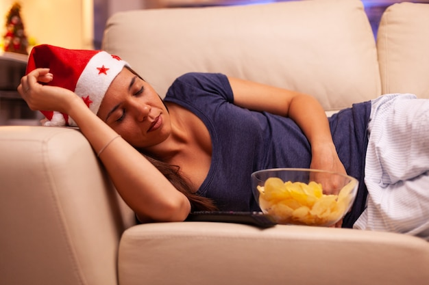 Chica dormida en el sofá en la cocina decorada de navidad