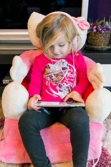 Chica dulce en tableta de navegación de auriculares