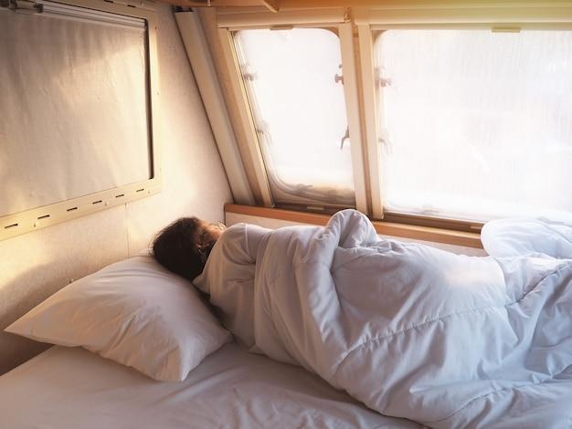 Chica durmiendo en la cama en el dormitorio móvil del coche