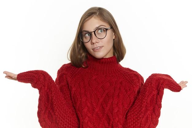 Chica elegante en anteojos y suéter encogiéndose de hombros, perdida, no sabe cómo responder, mirando hacia arriba con expresión facial indiferente despistada. woamn joven confundido posando