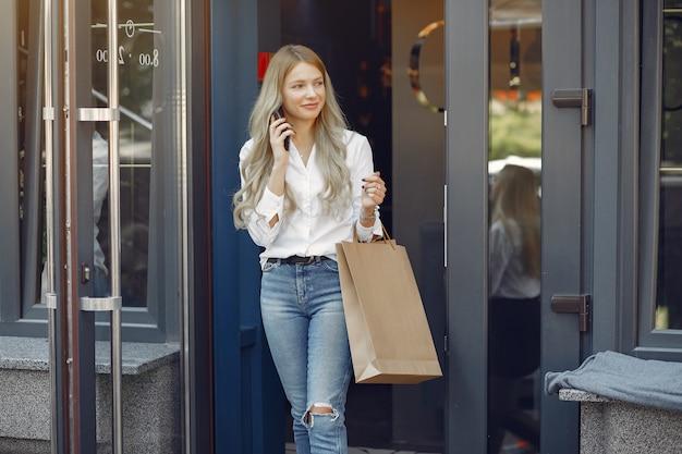 Chica elegante con bolsa de compras en una ciudad